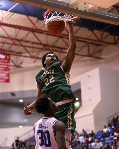Senior Elijah Caldwell defends the basket as DeSoto's Marques Bolden dunks during a tough district loss. Photo By Cynthia Rangel