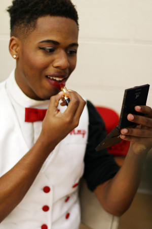 Senior Damian McElwee applies the High Hat's traditional red lipstick. (Photo by Karla Estrada)